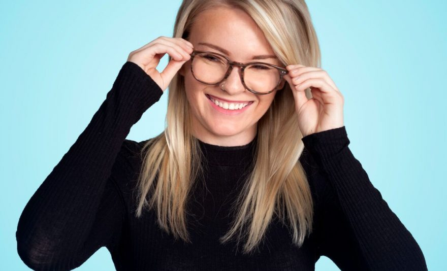 woman smiling with blond hair taking off Violet glasses