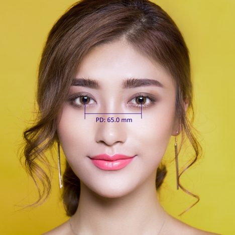 Young woman with brown hair. Graphic showing pupillary distance measurement.